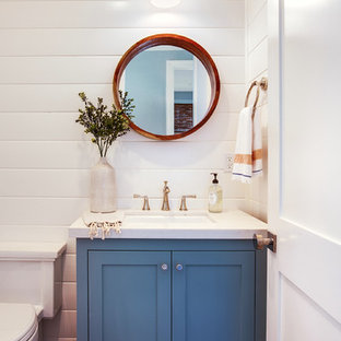 Пример оригинального дизайна: туалет в морском стиле с фасадами в стиле шейкер, синими фасадами, унитазом-моноблоком, белой плиткой, белыми стенами, паркетным полом среднего тона, врезной раковиной, столешницей из искусственного кварца и белой столешницей