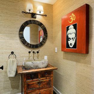 На фото: туалет среднего размера в восточном стиле с фасадами островного типа, искусственно-состаренными фасадами, унитазом-моноблоком, бежевыми стенами, паркетным полом среднего тона, настольной раковиной, столешницей из дерева, коричневым полом, разноцветной столешницей, напольной тумбой и обоями на стенах с