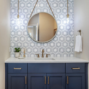 Idées déco pour un petit WC et toilettes bord de mer avec un placard à porte shaker, des portes de placard bleues, un carrelage blanc, du carrelage en marbre, un mur gris, un sol en bois brun, un lavabo encastré, un plan de toilette en quartz modifié, un sol marron et un plan de toilette blanc.