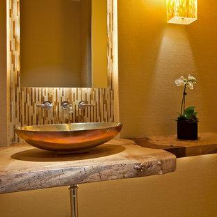 На фото: маленький туалет в стиле модернизм с настольной раковиной, столешницей из дерева, разноцветной плиткой, удлиненной плиткой, разноцветными стенами, полом из бамбука и коричневой столешницей