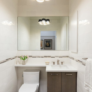 Example of a small trendy ceramic tile and white tile ceramic tile powder room design in New York with flat-panel cabinets, medium tone wood cabinets, quartz countertops, a one-piece toilet, white walls and an undermount sink
