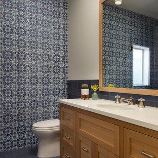 Cette photo montre un grand WC et toilettes chic avec un carrelage bleu, un lavabo encastré, des carreaux de céramique, un sol en carrelage de céramique, un sol bleu, un placard avec porte à panneau encastré, des portes de placard en bois clair, un WC à poser, un mur multicolore, un plan de toilette en stéatite et un plan de toilette blanc.