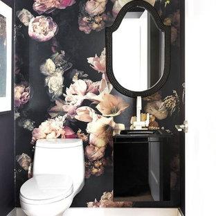 Idee per un piccolo bagno di servizio vittoriano con ante lisce, ante nere, WC monopezzo, pareti nere, parquet chiaro e lavabo integrato