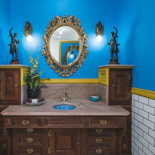 Пример оригинального дизайна: туалет в викторианском стиле с фасадами островного типа, темными деревянными фасадами, синими стенами, врезной раковиной и коричневой столешницей