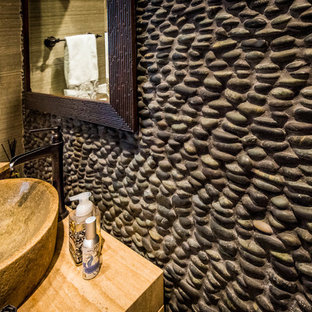 Modelo de aseo rústico, pequeño, con puertas de armario de madera clara, paredes beige, lavabo sobreencimera y encimera de travertino