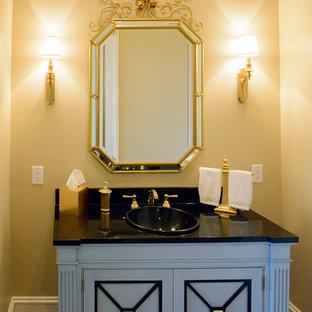Foto di un bagno di servizio contemporaneo con lavabo da incasso, ante con bugna sagomata, ante blu, top in granito, piastrelle nere e pareti beige