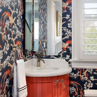 Réalisation d'un petit WC et toilettes tradition avec un placard à porte shaker, un lavabo encastré, un plan de toilette en quartz modifié, des portes de placard rouges, un mur multicolore, un plan de toilette blanc, meuble-lavabo encastré et du papier peint.