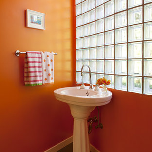 Inspiration for a beach style powder room remodel in San Francisco with a pedestal sink and orange walls