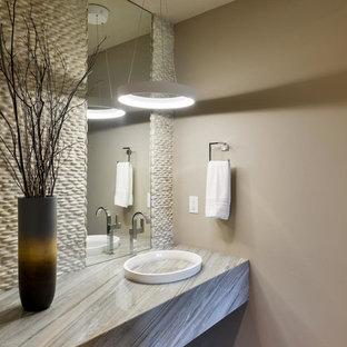 デンバーの中くらいのコンテンポラリースタイルのおしゃれなトイレ・洗面所 (ベージュの壁、一体型シンク、御影石の洗面台、グレーのタイル、石タイル) の写真