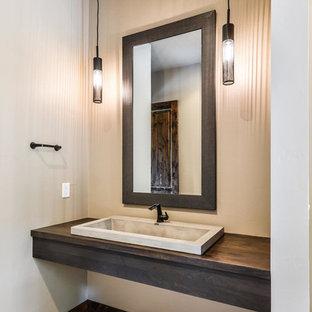 На фото: с высоким бюджетом туалеты среднего размера в современном стиле с раздельным унитазом, бежевыми стенами, накладной раковиной, столешницей из дерева, бежевым полом и коричневой столешницей