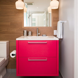 バンクーバーのトランジショナルスタイルのおしゃれなトイレ・洗面所 (フラットパネル扉のキャビネット、赤いキャビネット、白い洗面カウンター) の写真