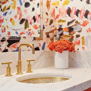 Inredning av ett eklektiskt toalett, med orange skåp och marmorbänkskiva