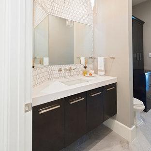 На фото: большой туалет в стиле модернизм с плоскими фасадами, темными деревянными фасадами, раздельным унитазом, белой плиткой, керамической плиткой, бежевыми стенами, полом из керамогранита, накладной раковиной, столешницей из искусственного камня и бежевым полом