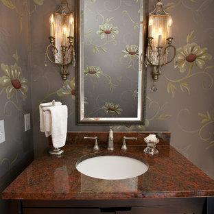 Eklektisk inredning av ett litet röd rött badrum, med möbel-liknande, skåp i mörkt trä, en toalettstol med separat cisternkåpa, flerfärgade väggar, ett undermonterad handfat och granitbänkskiva