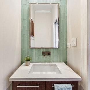 Пример оригинального дизайна: маленький туалет в современном стиле с плоскими фасадами, стеклянной плиткой, врезной раковиной, темными деревянными фасадами, зеленой плиткой, белыми стенами, белой столешницей, унитазом-моноблоком, темным паркетным полом и коричневым полом