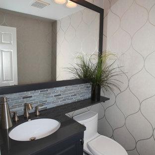 Cette photo montre un petit WC et toilettes chic avec un lavabo encastré, un placard avec porte à panneau surélevé, des portes de placard grises, un plan de toilette en quartz modifié, un WC à poser, un carrelage multicolore, un mur gris, un sol en bois foncé et des carreaux en allumettes.