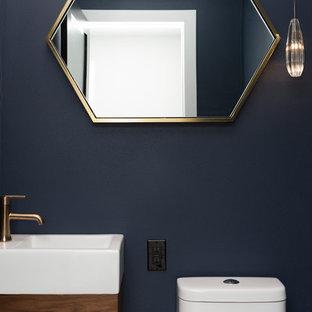 Aménagement d'un petit WC et toilettes moderne avec un placard à porte plane, des portes de placard marrons, un WC à poser, un mur bleu, un sol en carrelage de porcelaine, un lavabo suspendu, un plan de toilette en surface solide et un sol blanc.