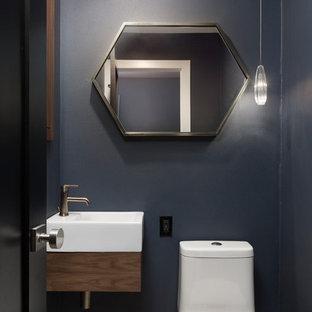 Modelo de aseo actual, pequeño, con armarios con paneles lisos, puertas de armario marrones, sanitario de una pieza, paredes azules, suelo de baldosas de porcelana, lavabo suspendido y suelo beige