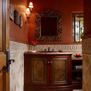 Esempio di un bagno di servizio mediterraneo di medie dimensioni con ante con riquadro incassato, ante in legno bruno, piastrelle beige, lastra di pietra, pareti rosse, pavimento in cementine, lavabo sottopiano e top in marmo