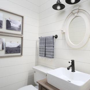 Modelo de aseo campestre con armarios con paneles empotrados, puertas de armario de madera oscura, sanitario de dos piezas, baldosas y/o azulejos blancos, paredes blancas, lavabo sobreencimera, encimera de madera y encimeras marrones