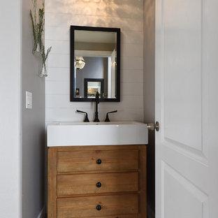 Modelo de aseo campestre, pequeño, con armarios con paneles lisos, puertas de armario marrones, paredes grises, suelo de madera en tonos medios, lavabo integrado y suelo marrón