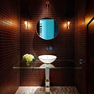 Ejemplo de aseo contemporáneo con lavabo sobreencimera, encimera de vidrio, baldosas y/o azulejos marrones y paredes marrones