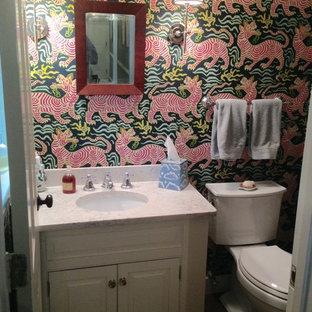 Aménagement d'un petit WC et toilettes moderne avec un placard avec porte à panneau surélevé, des portes de placard blanches, un WC séparé, un mur multicolore, un lavabo encastré et un plan de toilette en quartz modifié.