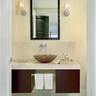 На фото: туалет в современном стиле с настольной раковиной, плоскими фасадами, фасадами цвета дерева среднего тона, бежевыми стенами, полом из галечной плитки, мраморной столешницей и бежевым полом