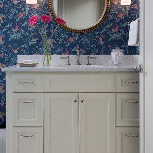 Aménagement d'un WC et toilettes classique avec un placard avec porte à panneau encastré, des portes de placard beiges, un mur multicolore, un sol en carrelage de terre cuite, un sol multicolore et un plan de toilette gris.