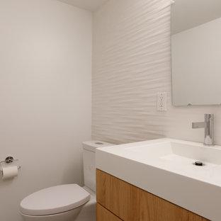 Inspiration pour un WC et toilettes design avec un placard à porte plane, des portes de placard en bois brun, un carrelage blanc, des carreaux de céramique, un mur blanc, une grande vasque et un plan de toilette en quartz.