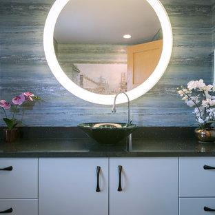 Modelo de aseo asiático, pequeño, con armarios tipo mueble, puertas de armario grises, paredes azules, lavabo sobreencimera y encimera de cuarzo compacto