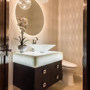 ロサンゼルスの中くらいのコンテンポラリースタイルのおしゃれなトイレ・洗面所 (フラットパネル扉のキャビネット、濃色木目調キャビネット、分離型トイレ、白いタイル、トラバーチンの床、ベッセル式洗面器、ガラスの洗面台、ベージュの壁、白い洗面カウンター) の写真