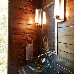 На фото: маленький туалет в стиле модернизм с фасадами островного типа, коричневой плиткой, плиткой мозаикой, коричневыми стенами, полом из керамогранита, настольной раковиной, столешницей из кварцита, серым полом, черной столешницей, напольной тумбой и панелями на части стены с