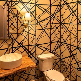 На фото: маленький туалет в современном стиле с раздельным унитазом, разноцветными стенами, подвесной раковиной, столешницей из дерева и коричневой столешницей