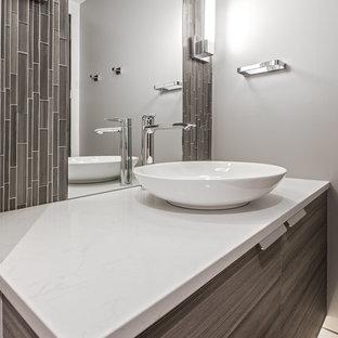 На фото: туалет среднего размера в современном стиле с плоскими фасадами, темными деревянными фасадами, коричневой плиткой, плиткой мозаикой, серыми стенами, полом из травертина, настольной раковиной, мраморной столешницей, бежевым полом и белой столешницей с