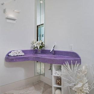マイアミのトロピカルスタイルのおしゃれなトイレ・洗面所 (オープンシェルフ、白いキャビネット、白い壁、一体型シンク、ベージュの床、紫の洗面カウンター) の写真