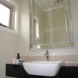 На фото: туалет среднего размера в современном стиле с фасадами островного типа, светлыми деревянными фасадами, унитазом-моноблоком, бежевой плиткой, каменной плиткой, бежевыми стенами, полом из керамической плитки, накладной раковиной и столешницей из ламината с