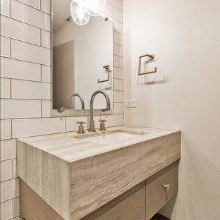 Diseño de aseo de estilo de casa de campo, de tamaño medio, con paredes blancas, suelo gris, armarios con paneles lisos, baldosas y/o azulejos blancos, lavabo bajoencimera, encimera de travertino y encimeras beige