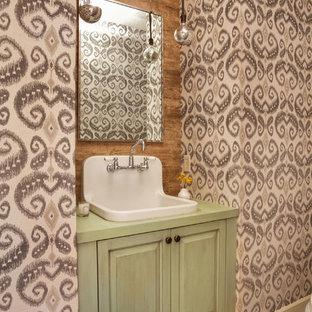 Aménagement d'un petit WC et toilettes classique avec un placard avec porte à panneau surélevé, des portes de placards vertess, un mur marron, un sol en marbre, un plan de toilette en bois et un plan de toilette vert.