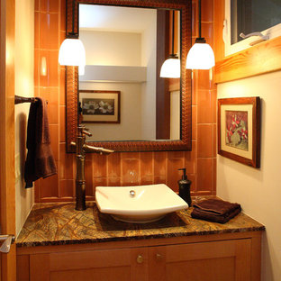 Inspiration pour un petit WC et toilettes ethnique avec un placard à porte shaker, un WC à poser, un carrelage marron, des carreaux de céramique, une vasque, un plan de toilette en marbre, un mur beige et des portes de placard en bois brun.