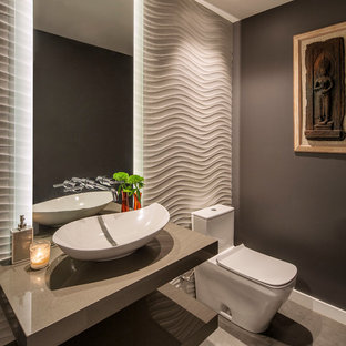 Idéer för funkis grått toaletter, med öppna hyllor, en toalettstol med hel cisternkåpa, grå väggar, betonggolv, ett fristående handfat, bänkskiva i akrylsten och grått golv