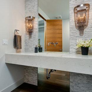 Cette image montre un WC et toilettes design avec un lavabo intégré, un carrelage gris, un carrelage de pierre, un sol en bois foncé, un mur blanc et un plan de toilette blanc.