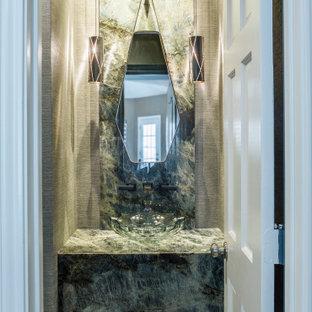 Cette image montre un petit WC et toilettes design avec un mur beige, un sol en carrelage de terre cuite, une vasque, un sol turquoise, des portes de placard turquoises, un plan de toilette en verre, un plan de toilette vert et meuble-lavabo encastré.