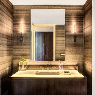 Aménagement d'un WC et toilettes contemporain avec un placard à porte plane, des portes de placard marrons, un mur marron, un lavabo suspendu, un sol noir et un plan de toilette blanc.