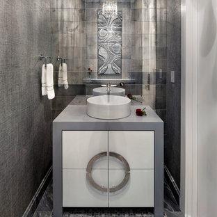 Modern inredning av ett litet toalett, med släta luckor, vita skåp, flerfärgad kakel, spegel istället för kakel, grå väggar, mosaikgolv, ett fristående handfat, bänkskiva i akrylsten och grått golv
