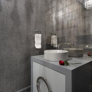 Пример оригинального дизайна: маленький туалет в современном стиле с плоскими фасадами, белыми фасадами, разноцветной плиткой, зеркальной плиткой, серыми стенами, полом из мозаичной плитки, настольной раковиной, столешницей из искусственного камня и серым полом
