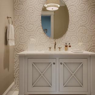 Пример оригинального дизайна: туалет среднего размера в стиле современная классика с керамогранитной плиткой, бежевыми стенами, полом из керамической плитки, врезной раковиной, столешницей из искусственного камня, серыми фасадами, фасадами с утопленной филенкой и белой столешницей