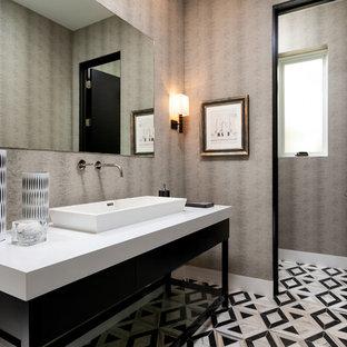 Стильный дизайн: большой туалет в современном стиле с настольной раковиной, разноцветным полом, белой столешницей, плоскими фасадами, черными фасадами, серыми стенами и полом из керамогранита - последний тренд