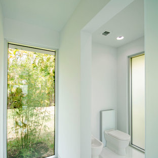 Mid-sized minimalist porcelain tile and white floor powder room photo in Miami with a bidet and white walls