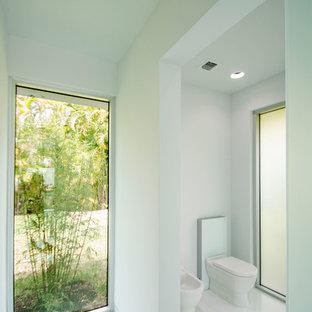 Modelo de aseo minimalista, de tamaño medio, con bidé, paredes blancas, suelo de baldosas de porcelana y suelo blanco